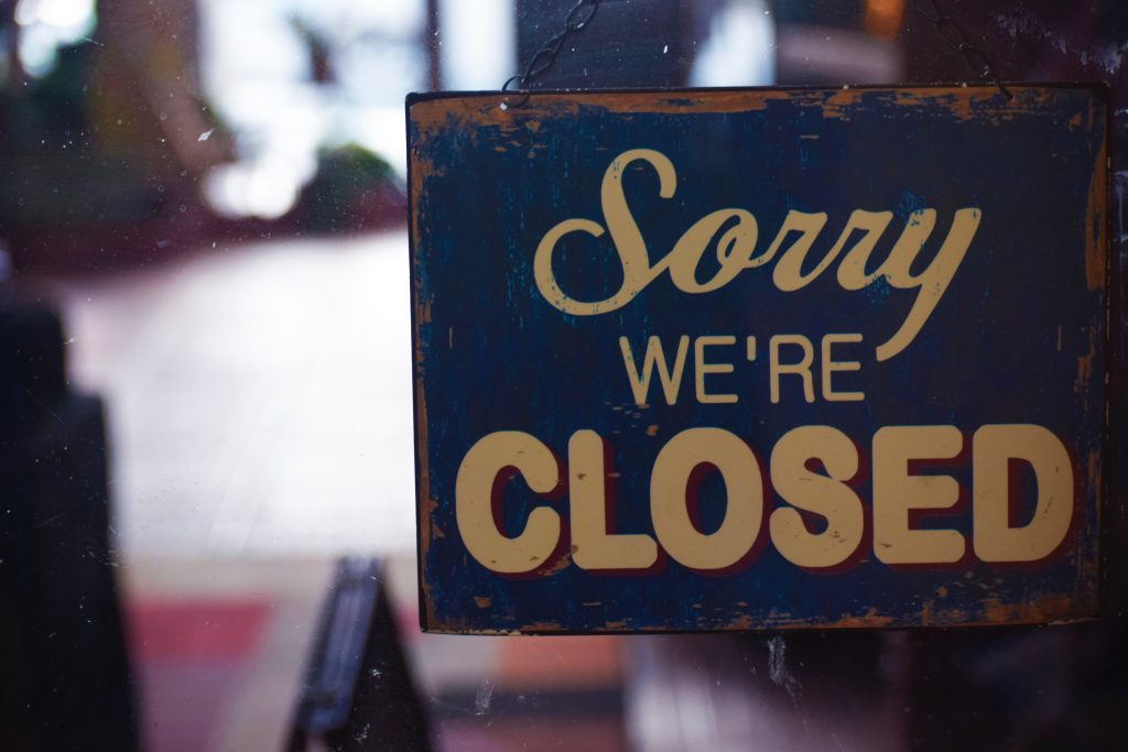 "A weathered blue sign reading, ""Sorry, We're Closed"" hangs in a shop window. The sign is blue with cream-colored lettering edged in red"